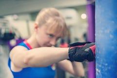 Νέα εγκιβωτίζοντας γάντια διατρήσεων κατάρτισης γυναικών για punching την τσάντα Κορίτσι που κάνει το ισχυρό λάκτισμα Διαγώνια τα στοκ φωτογραφία με δικαίωμα ελεύθερης χρήσης