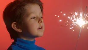 Νέα εκμετάλλευση αγοριών που καίει sparkler στο κόκκινο υπόβαθρο φιλμ μικρού μήκους