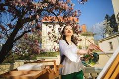 Νέα εκμετάλλευση καλλιτεχνών γυναικών brunette στα χέρια μια βούρτσα και μια παλέτα Κοντά σε την το δέντρο magnolia και ο διάφορο στοκ εικόνα