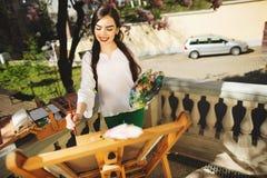 Νέα εκμετάλλευση καλλιτεχνών γυναικών brunette στα χέρια μια βούρτσα και μια παλέτα Κοντά σε την το δέντρο magnolia και ο διάφορο στοκ φωτογραφίες