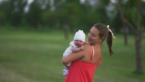 Νέα εκμετάλλευση μητέρων και παιχνίδι με το παιδί αγοράκι της στο πάρκο πόλεων που στέκεται φορώντας το φωτεινό κόκκινο φόρεμα -  φιλμ μικρού μήκους