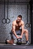 Νέα εκμετάλλευση ατόμων αθλητών kettlebell στο πάτωμα γυμναστικής ενάντια στο τουβλότοιχο Στοκ φωτογραφία με δικαίωμα ελεύθερης χρήσης
