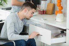 Νέα εκτός λειτουργίας συνεδρίαση ατόμων στην αναπηρική καρέκλα που λειτουργεί στην κουζίνα Στοκ Εικόνα