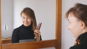 Νέα ελκυστικά καφετής-μαλλιαρά χαμόγελα γυναικών που κτενίζουν την τρίχα της μπροστά από τον καθρέφτη στο σπίτι απόθεμα βίντεο