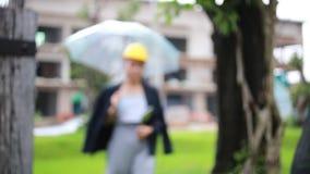 Νέα ελκυστική γυναίκα με το κτήριο ομπρελών κάτω από την οικοδόμηση απόθεμα βίντεο