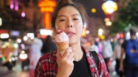 Νέα ελκυστική γυναίκα που απολαμβάνει το παγωτό φραουλών στον κώνο βαφλών κατά τη διάρκεια να εξισώσει τη νύχτα την αγορά απόθεμα βίντεο