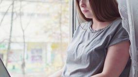 Νέα ελκυστική γυναίκα που εργάζεται στο lap-top στο σπίτι απόθεμα βίντεο