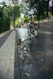 Νέα ελκυστική γυναίκα που οδηγά ένα ποδήλατο στοκ φωτογραφία