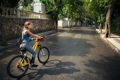 Νέα ελκυστική γυναίκα που οδηγά ένα ποδήλατο στοκ φωτογραφία με δικαίωμα ελεύθερης χρήσης