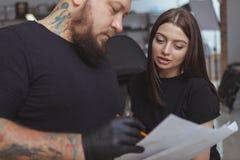 Νέα ελκυστική γυναίκα που παίρνει τη νέα δερματοστιξία από το επαγγελματικό tattooist στοκ εικόνες με δικαίωμα ελεύθερης χρήσης