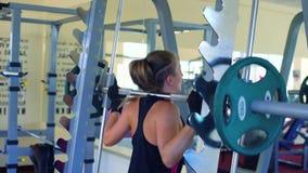 Νέα ελκυστική γυναίκα στα προστατευτικά γάντια που λειτουργούν σκληρά να κάνει τις σταθμισμένες στάσεις οκλαδόν στη γυμναστική φιλμ μικρού μήκους