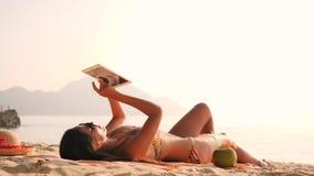 Νέα ελκυστική γυναίκα στο μπικίνι χρησιμοποιώντας την κινητή συσκευή ταμπλετών και κάνοντας ηλιοθεραπεία στην τροπική παραλία παρ απόθεμα βίντεο