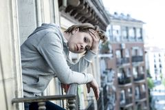 Νέα ελκυστική δυστυχισμένη γυναίκα με την κατάθλιψη και την ανησυχία που αισθάνεται άθλια και μάταιη στο εγχώριο μπαλκόνι Στοκ Φωτογραφίες