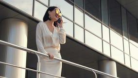Νέα ελκυστική επιχειρηματίας στο άσπρο πουκάμισο και το μαύρο κοστούμι που περπατά κάτω από την οδό κατά μήκος της ράγας χεριών ε απόθεμα βίντεο