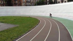 Νέα ελκυστική θηλυκή κατάρτιση ποδηλατών στο ποδηλατοδρόμιο Αθλητικό κορίτσι στο κράνος που οδηγά στην ανακύκλωση της διαδρομής Γ απόθεμα βίντεο