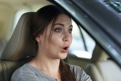 Νέα ελκυστική καυκάσια γυναίκα πίσω από τη ρόδα που οδηγεί ένα αυτοκίνητο με το μορφασμό της κατάπληξης ή του κλονισμού, στόμα πο στοκ εικόνες