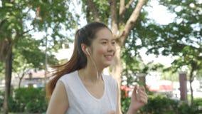 Νέα ελκυστική μουσική ακούσματος γυναικών στο ακουστικό τρέχοντας στο πράσινο πάρκο πόλεων φιλμ μικρού μήκους