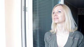 Νέα ελκυστική νοικοκυρά, ξανθή γυναίκα που στέκεται κοντά στο ανοικτό παράθυρο, κοιτάζοντας έξω για κάποιο, που κυματίζει το χέρι φιλμ μικρού μήκους