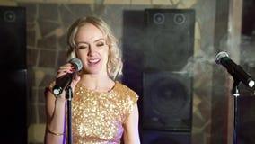Νέα ελκυστική ξανθή γυναίκα που χορεύει και που τραγουδά με το μικρόφωνο φιλμ μικρού μήκους