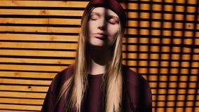 Νέα ελκυστική ξανθή τοποθέτηση κοριτσιών μπροστά από τον ξύλινο τοίχο, σκιά κλουβιών απόθεμα βίντεο