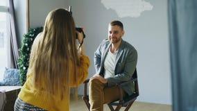 Νέα ελκυστική πρότυπη τοποθέτηση ανδρών για τη γυναίκα φωτογράφων ενώ πυροβολεί με μια ψηφιακή κάμερα στο στούντιο φωτογραφιών φιλμ μικρού μήκους