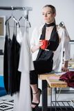 νέα ελκυστική συνεδρίαση σχεδιαστών μόδας στο γραφείο εργασίας με το φλιτζάνι του καφέ και το κοίταγμα στοκ εικόνες