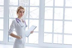 Νέα ενήλικη ελκυστική στάση γιατρών γυναικών με το έγγραφο εγγράφων Στοκ Εικόνες
