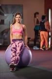 Νέα ενήλικη φίλαθλη τοποθέτηση γυναικών στο fitball Στοκ Εικόνες