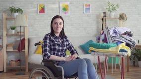 Νέα ενδύματα πλύσης νοικοκυρών με ειδικές ανάγκες γυναικών, οικιακά, εξετάζοντας τη κάμερα, χαμόγελο απόθεμα βίντεο