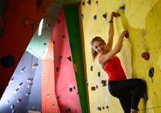 Νέα ενεργός γυναίκα Bouldering στο ζωηρόχρωμο τεχνητό βράχο στην αναρρίχηση της γυμναστικής Ακραίος αθλητισμός και εσωτερική έννο στοκ φωτογραφία