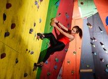 Νέα ενεργός γυναίκα Bouldering στο ζωηρόχρωμο τεχνητό βράχο στην αναρρίχηση της γυμναστικής Ακραίος αθλητισμός και εσωτερική έννο στοκ φωτογραφίες με δικαίωμα ελεύθερης χρήσης