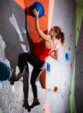 Νέα ενεργός γυναίκα Bouldering στο ζωηρόχρωμο τεχνητό βράχο στην αναρρίχηση της γυμναστικής Ακραίος αθλητισμός και εσωτερική έννο στοκ φωτογραφία με δικαίωμα ελεύθερης χρήσης