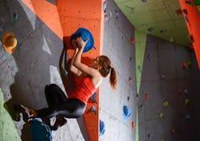 Νέα ενεργός γυναίκα Bouldering στο ζωηρόχρωμο τεχνητό βράχο στην αναρρίχηση της γυμναστικής Ακραίος αθλητισμός και εσωτερική έννο στοκ εικόνα με δικαίωμα ελεύθερης χρήσης