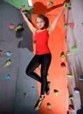 Νέα ενεργός γυναίκα Bouldering στο ζωηρόχρωμο τεχνητό βράχο στην αναρρίχηση της γυμναστικής Ακραίος αθλητισμός και εσωτερική έννο στοκ εικόνα