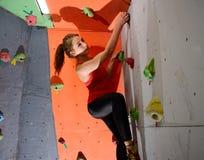 Νέα ενεργός γυναίκα Bouldering στο ζωηρόχρωμο τεχνητό βράχο στην αναρρίχηση της γυμναστικής Ακραίος αθλητισμός και εσωτερική έννο στοκ εικόνες