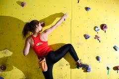 Νέα ενεργός γυναίκα Bouldering στο ζωηρόχρωμο τεχνητό βράχο στην αναρρίχηση της γυμναστικής Ακραίος αθλητισμός και εσωτερική έννο στοκ εικόνες με δικαίωμα ελεύθερης χρήσης