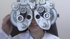 Νέα εξέταση ματιών γυναικών optometrist στον οφθαλμολόγο που χρησιμοποιεί phoropter στενό επάνω Χαριτωμένα χαμόγελα γυναικών που  απόθεμα βίντεο