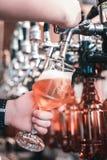 Νέα επαγγελματικά γυαλιά πλήρωσης μπάρμαν των πελατών με την μπύρα τεχνών στοκ εικόνες