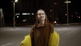 Νέα επεκτατική γυναίκα που χορεύει sensually έξω στο κίτρινο σακάκι Αισθανθείτε ελεύθερος, χαμόγελο Μήκος σε πόδηα Handhelded απόθεμα βίντεο