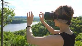 Νέα επικεφαλής-τοποθετημένη χρήσεις επίδειξη γυναικών στο πάρκο Παίζοντας παιχνίδι που χρησιμοποιεί το VR-κράνος για τα έξυπνα τη απόθεμα βίντεο