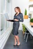 Νέα επιτυχής επιχειρηματίας με το φορητό προσωπικό υπολογιστή που στέκεται κοντά στο παράθυρο ταμπλέτα υπολογιστών πο&upsi Επιχεί Στοκ Εικόνα