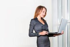 Νέα επιτυχής επιχειρηματίας με το φορητό προσωπικό υπολογιστή που στέκεται κοντά στο παράθυρο ταμπλέτα υπολογιστών πο&upsi Επιχεί Στοκ φωτογραφία με δικαίωμα ελεύθερης χρήσης