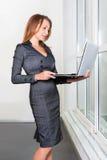 Νέα επιτυχής επιχειρηματίας με το φορητό προσωπικό υπολογιστή που στέκεται κοντά στο παράθυρο ταμπλέτα υπολογιστών πο&upsi Επιχεί Στοκ Φωτογραφία