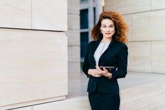 Νέα επιτυχής επιχειρηματίας στα κομψά ενδύματα, που έχουν την άφθονη τρίχα, που κρατά την ταμπλέτα στα χέρια πηγαίνοντας για την  στοκ φωτογραφία με δικαίωμα ελεύθερης χρήσης