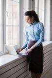 Νέα επιτυχής ευτυχής χαμογελώντας επιχειρησιακή γυναίκα στο lap-top στοκ φωτογραφίες