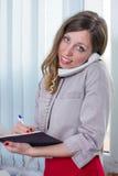 Νέα επιχειρηματίας με το σημειωματάριο στο τηλέφωνο Στοκ φωτογραφίες με δικαίωμα ελεύθερης χρήσης