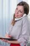 Νέα επιχειρηματίας με το σημειωματάριο στο τηλέφωνο Στοκ Φωτογραφία