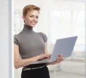 Νέα επιχειρηματίας με το φορητό προσωπικό υπολογιστή στο γραφείο στοκ εικόνα