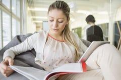 Νέα επιχειρηματίας με το ψηφιακό βιβλίο ανάγνωσης ταμπλετών στην αρχή Στοκ εικόνα με δικαίωμα ελεύθερης χρήσης