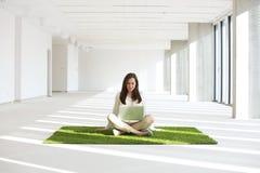 Νέα επιχειρηματίας με το lap-top καθμένος στον τάπητα χλόης στο κενό γραφείο Στοκ Εικόνες